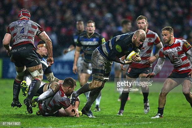 Matt Garvey of Bath is held up by Darren Dawidiuk of Gloucester as Bill Meakes closes in during the Aviva Premiership match between Gloucester and...