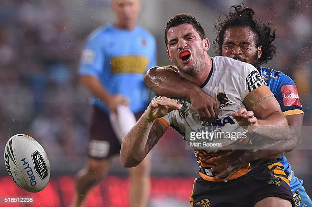 Matt Gillett of the Broncos knocks on in the tackle by Agnatius Paasi of the Titans during the round five NRL match between the Gold Coast Titans and...
