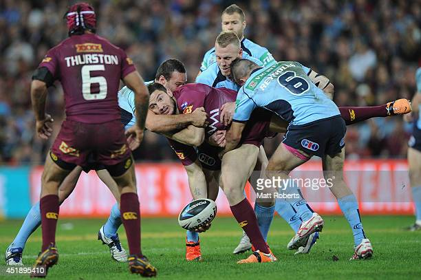 Matt Gillett of the Maroons offloads the ball in the tackle during game three of the State of Origin series between the Queensland Maroons and the...