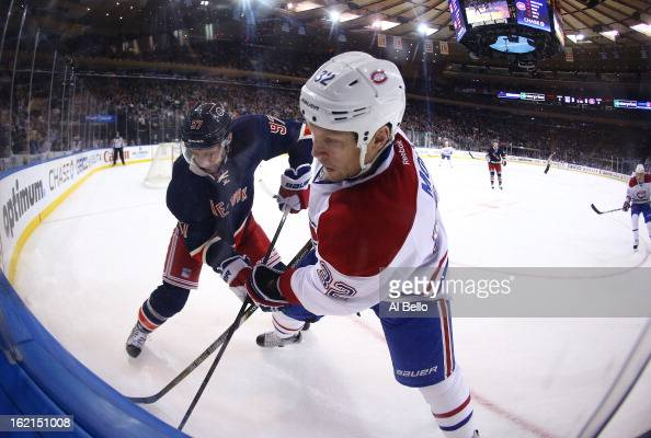 Matt Gilroy of the New York Rangers and Travis Moen of the Montreal Canadiens battle for the puck during their game at Madison Square Garden on...