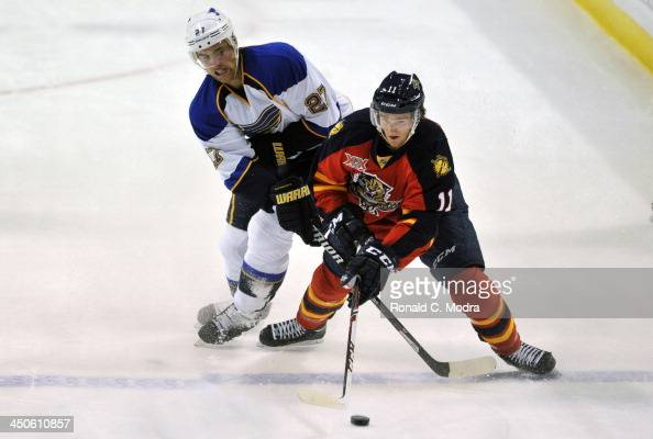 Matt Gilroy of the St Louis Blues crosses sticks with Jonathan Huberdeau of the Florida Panthers during a NHL game at the BBT Center on November 1...
