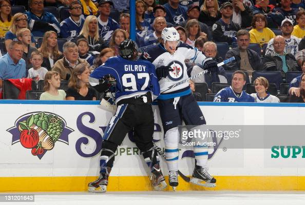 Matt Gilroy of the Tampa Bay Lightning checks Blake Wheeler of the Winnipeg Jets into the boards at the St Pete Times Forum on October 29 2011 in...