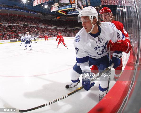 Matt Gilroy of the Tampa Bay Lightning looks to the play with Darren helm of the Detroit Red Wings during an NHL game at Joe Louis Arena on November...