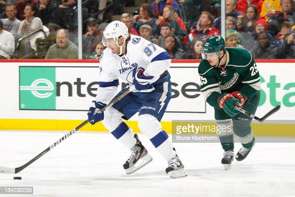 Matt Gilroy of the Tampa Bay Lightning skates with the puck with Nick Johnson of the Minnesota Wild defending during the game at the Xcel Energy...