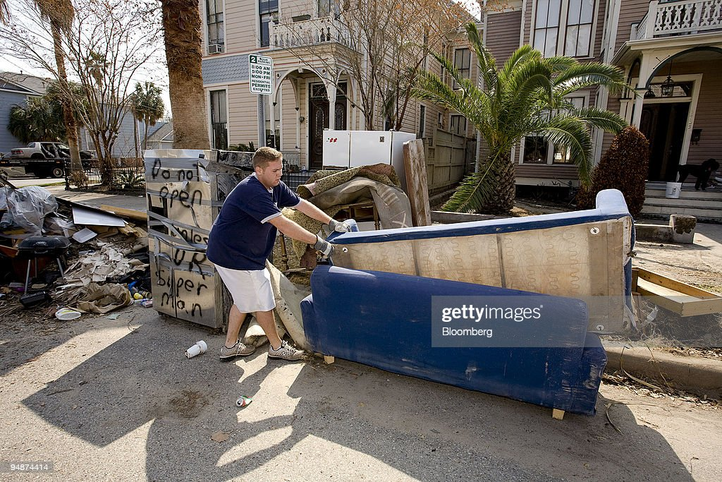 Matt Goff hauls a couch to the curb outside the home of his aunt in Galveston, Texas, U.S., on Saturday, Oct. 11, 2008. Hundreds of thousands of residents throughout the Houston and Galveston region are still assessing damage, some living in motels and shelters while repairs are made, after Hurricane Ike blasted ashore with a storm surge of up to 12 feet last month.