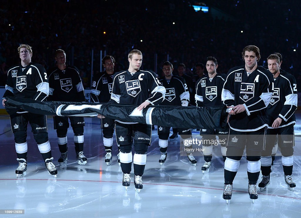 Matt Greene #2, Dustin Brown #23 and Anze Kopitar #11 of the Los Angeles Kings carry the 2011-12 Stanley Cup banner during a banner raising ceremony before the NHL season opening game against the Chicago Blackhawks at Staples Center on January 19, 2013 in Los Angeles, California.