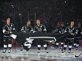 Matt Greene la28#3 Anze Kopitar and Dustin Brown of the Los Angeles Kings carry a Stanley Cup banner to be raised during a pre game ceremony before...
