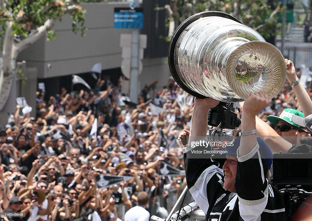 Matt Greene #2 of the Los Angeles Kings holds up the Stanley Cup to the fans during the Los Angeles Kings Stanley Cup Victory Parade on June 14, 2012 in Los Angeles, California.