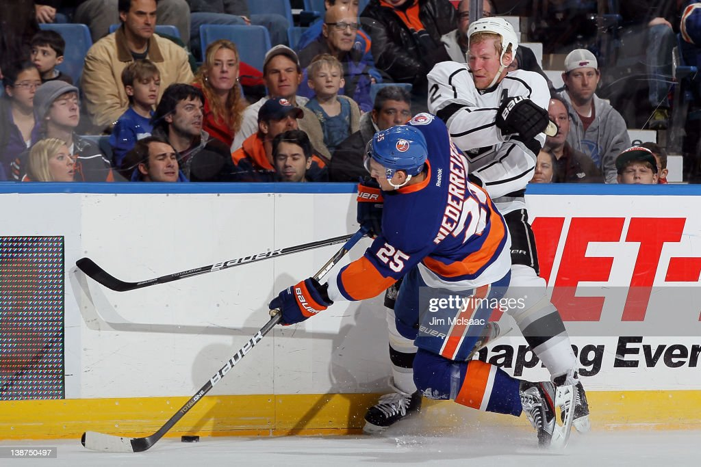 Matt Greene of the Los Angeles Kings lays a hard first period check against Nino Niederreiter of the New York Islanders on February 11 2012 at Nassau...