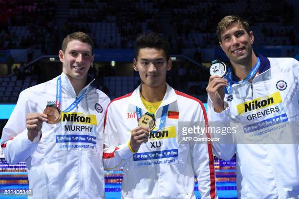 US Matt Grevers China's Xu Jiayu and US Ryan Murphy celebrate on the podium after the men's 100m backstroke final during the swimming competition at...