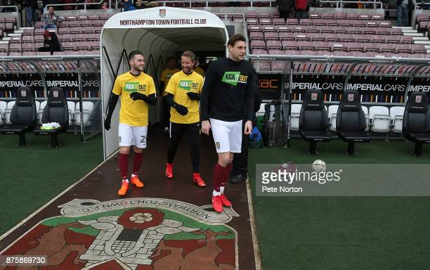 Matt Grimes Dean Bowditch and Ash Taylor of Northampton Town leave the players tunnel wearing Kick it Out Tee Shirts for the pre match warm up prior...