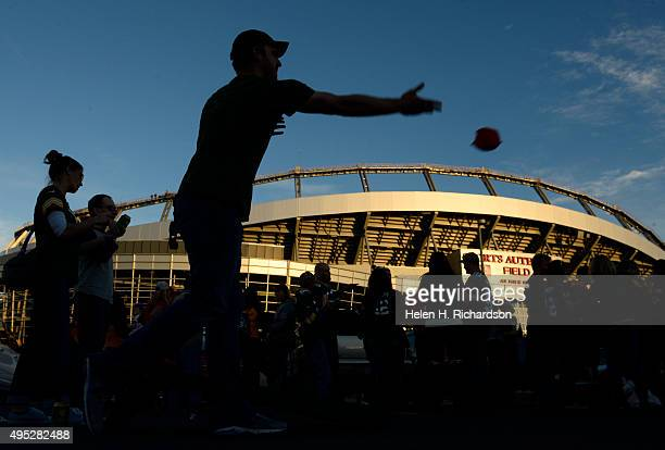 Matt Guth throws a bag while playing a corn hole game prior to the start of the game The Denver Broncos played the Green Bay Packers at Sports...