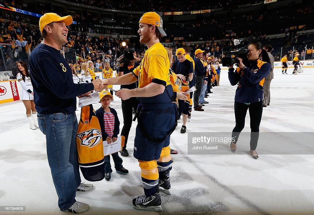 Matt Halischuk #24 of the Nashville Predators gives his game worn jersey to a fan following a win against the Calgary Flames during an NHL game at the Bridgestone Arena on April 23, 2013 in Nashville, Tennessee.