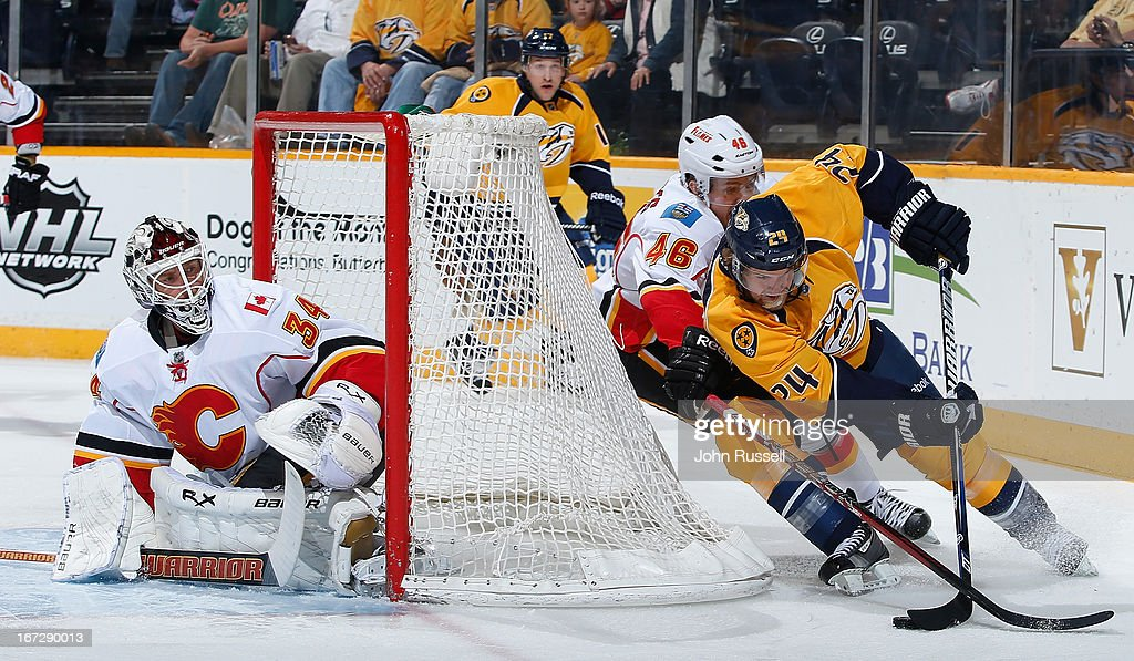 Matt Halischuk #24 of the Nashville Predators skates the puck around the net against Carter Bancks #46 and goalie Miikka Kiprusoff #34 of the Calgary Flames during an NHL game at the Bridgestone Arena on April 23, 2013 in Nashville, Tennessee.
