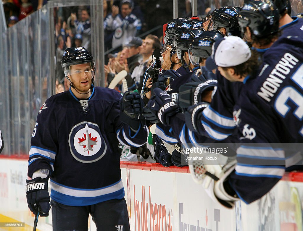 Matt Halischuk of the Winnipeg Jets celebrates his first period goal against the Dallas Stars with teammates at the bench at the MTS Centre on...
