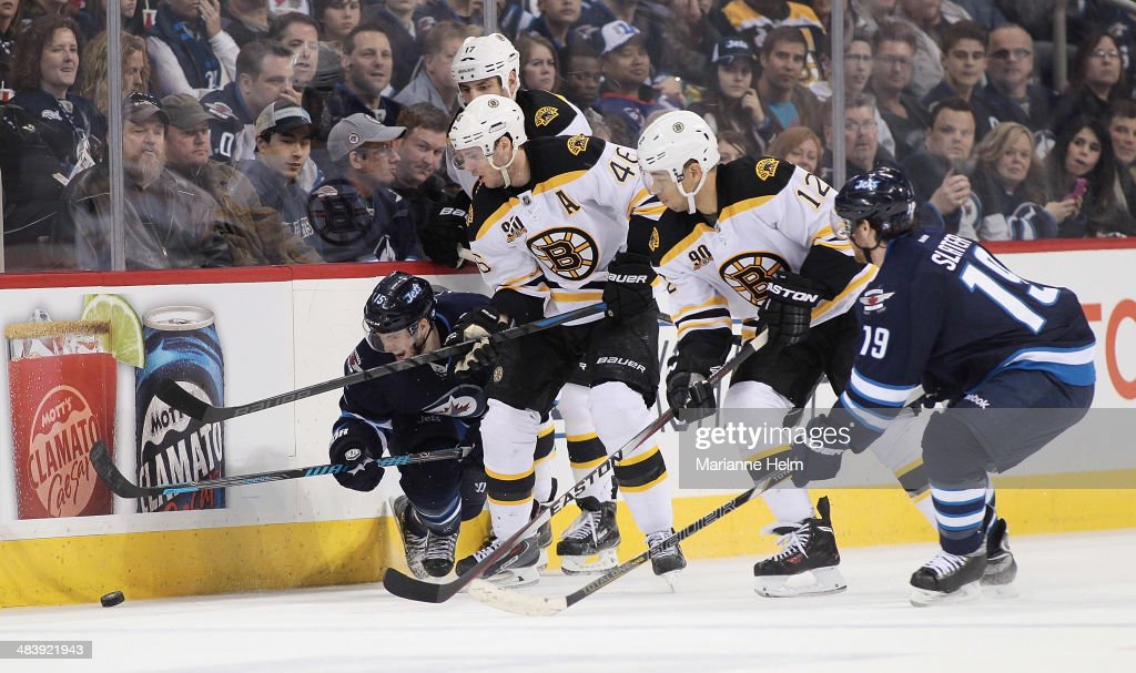 Matt Halischuk #15 of the Winnipeg Jets fights for the puck along the boards with David Krejci #46 and Jarome Iginla #12 of the Boston Bruins in second period action in an NHL game at the MTS Centre on April 10, 2014 in Winnipeg, Manitoba, Canada.