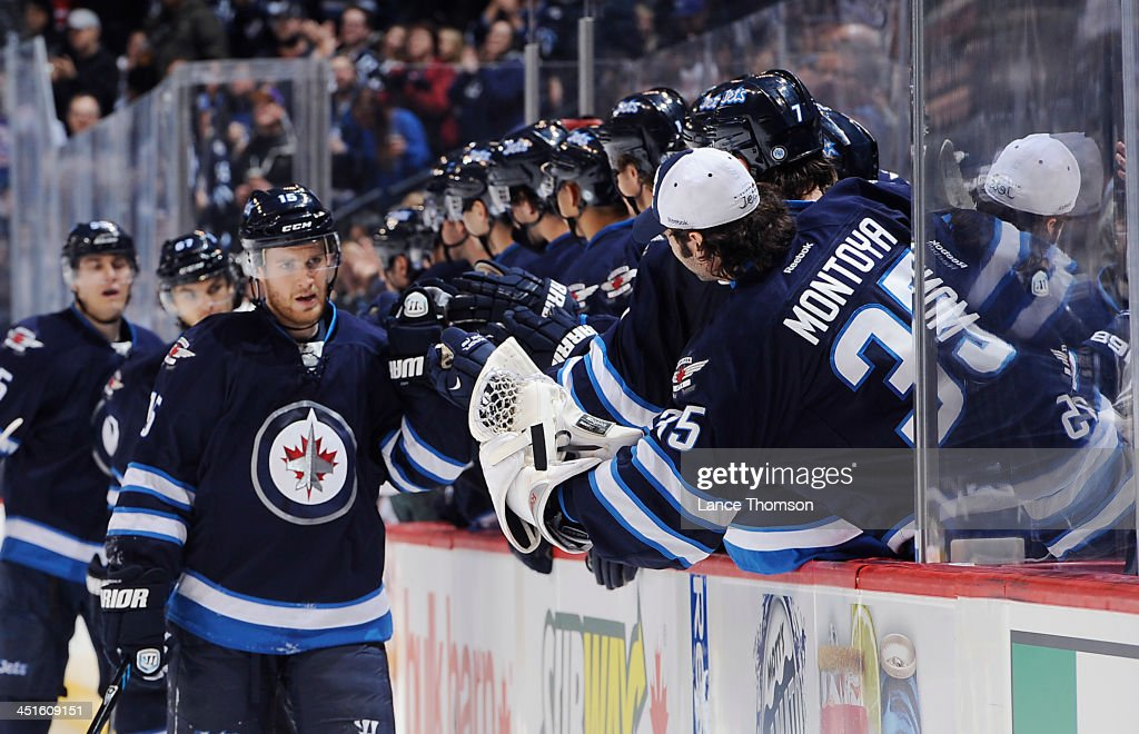 <a gi-track='captionPersonalityLinkClicked' href=/galleries/search?phrase=Matt+Halischuk&family=editorial&specificpeople=714406 ng-click='$event.stopPropagation()'>Matt Halischuk</a> #15 of the Winnipeg Jets gets congratulations from teammates at the bench after scoring a third period goal against the Minnesota Wild at the MTS Centre on November 23, 2013 in Winnipeg, Manitoba, Canada.