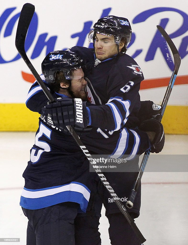 Matt Halischuk #15 of the Winnipeg Jets is congratulated by teammate Michael Frolik #67 after his goal in third period action in an NHL game against the Detroit Red Wings at the MTS Centre on November 4, 2013 in Winnipeg, Manitoba, Canada.