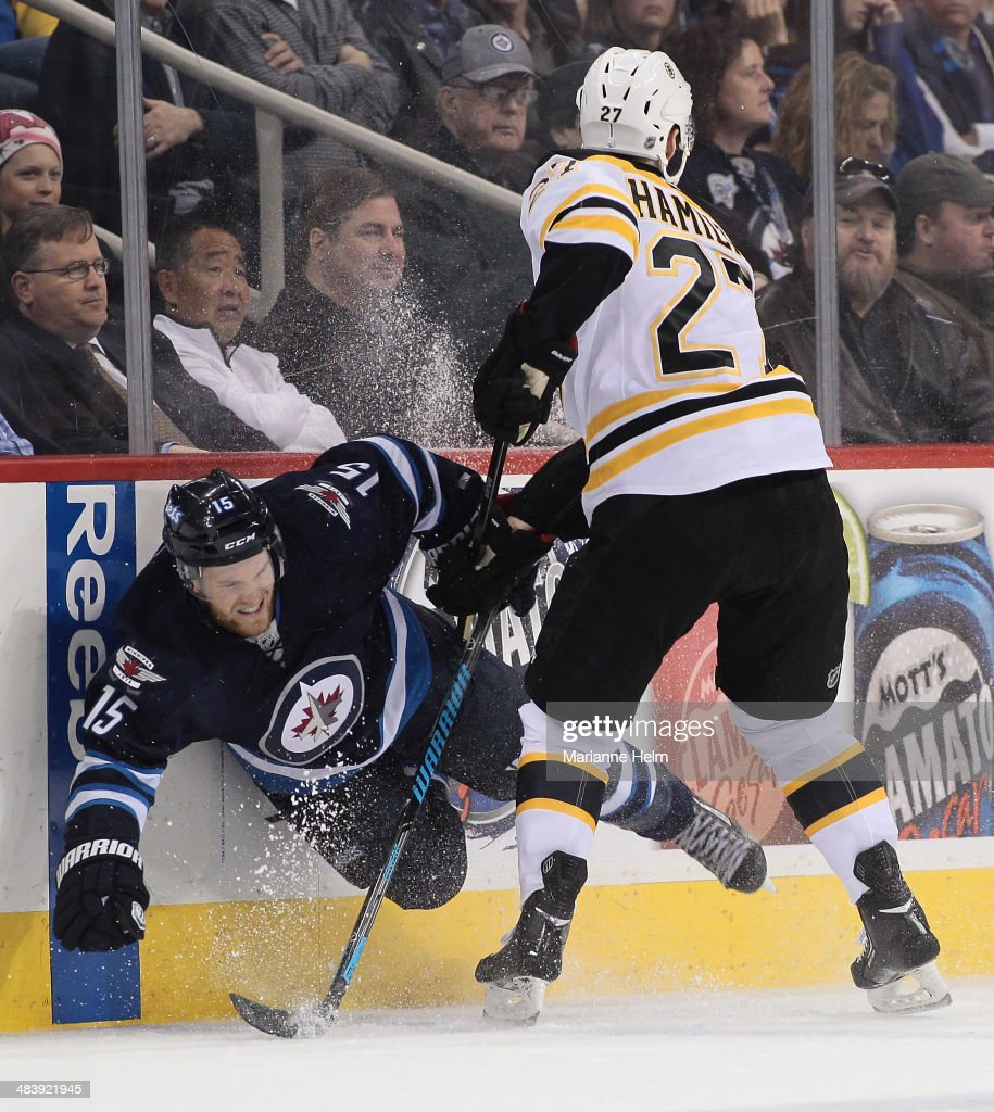 Matt Halischuk #15 of the Winnipeg Jets is taken to the boards by Dougie Hamilton #27 of the Boston Bruins in second period action in an NHL game at the MTS Centre on April 10, 2014 in Winnipeg, Manitoba, Canada.