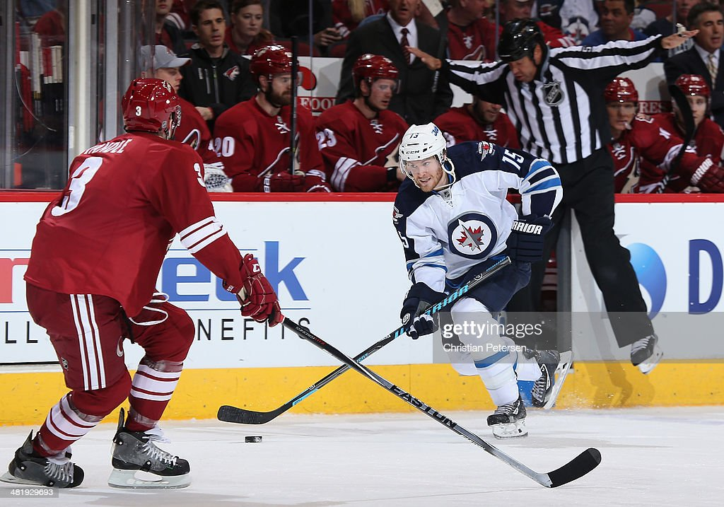 Matt Halischuk #15 of the Winnipeg Jets skates with the puck against Keith Yandle #3 of the Phoenix Coyotes during the third period of the NHL game at Jobing.com Arena on April 1, 2014 in Glendale, Arizona. The Jets defeated the Coyotes 2-1 in an overtime shootout.