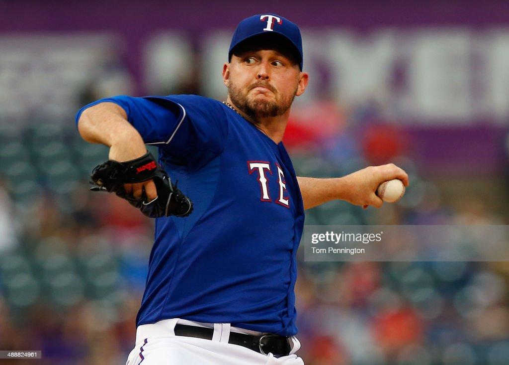 Matt Harrison #54 of the Texas Rangers pitches against the Colorado Rockies in the top of the first inning at Globe Life Park in Arlington on May 8, 2014 in Arlington, Texas.