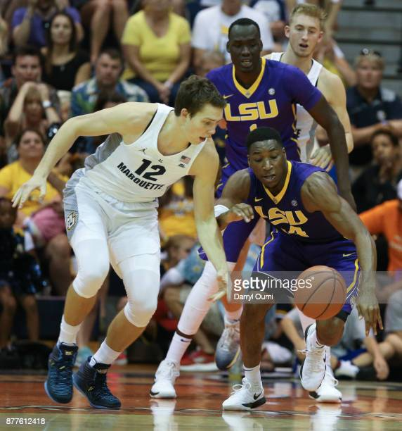 Matt Heldt of the Marquette Golden Eagles and Randy Onwuasor of the LSU Tigers chase after a loose ball during the first half of their game at the...