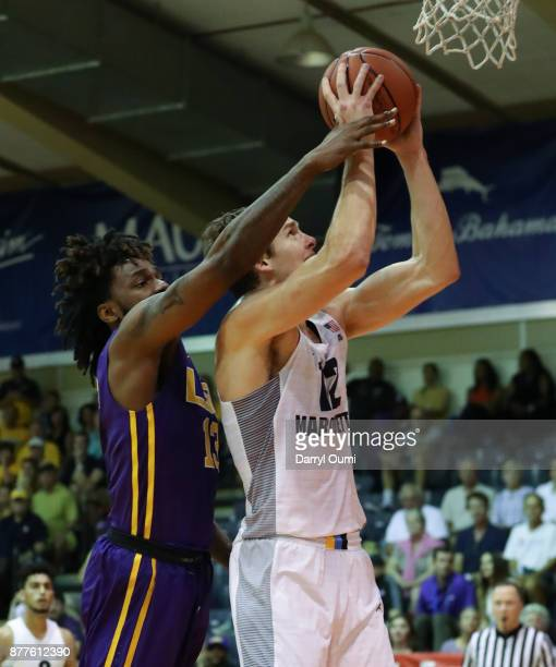 Matt Heldt of the Marquette Golden Eagles is fouled by Jeremy Combs of the LSU Tigers as he shoots during the first half of their game at the Maui...