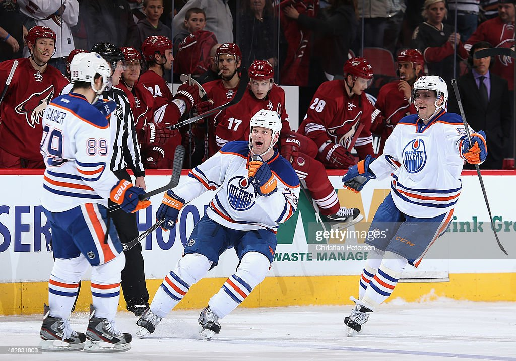 Matt Hendricks and David Perron of the Edmonton Oilers congratulate Sam Gagner after Gagner scored the game winning shootout goal against the Phoenix...