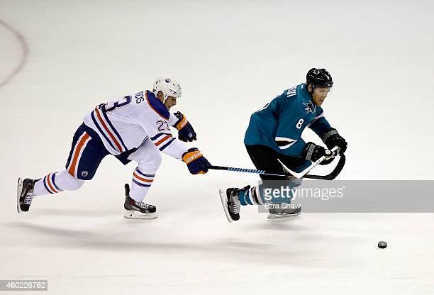 Matt Hendricks of the Edmonton Oilers and Joe Pavelski of the San Jose Sharks go for the puck at SAP Center on December 9 2014 in San Jose California