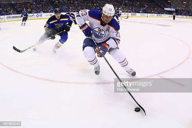 Matt Hendricks of the Edmonton Oilers beats Colton Parayko of the St Louis Blues to the loose puck at the Scottrade Center on October 8 2015 in St...