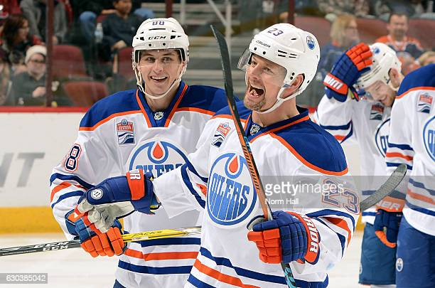 Matt Hendricks of the Edmonton Oilers celebrates with teammate Brandon Davidson after his second period goal against the Arizona Coyotes at Gila...