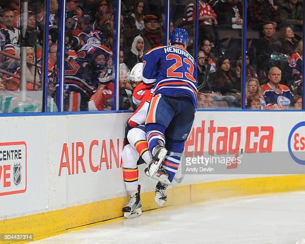 Matt Hendricks of the Edmonton Oilers lands a big hit on Aaron Ekblad of the Florida Panthers on January 10 2016 at Rexall Place in Edmonton Alberta...