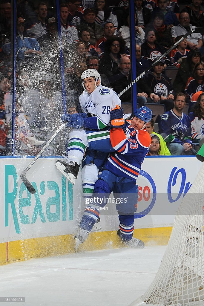 Matt Hendricks of the Edmonton Oilers lands a big hit on Frank Corrado of the Vancouver Canucks on April 12 2014 at Rexall Place in Edmonton Alberta...