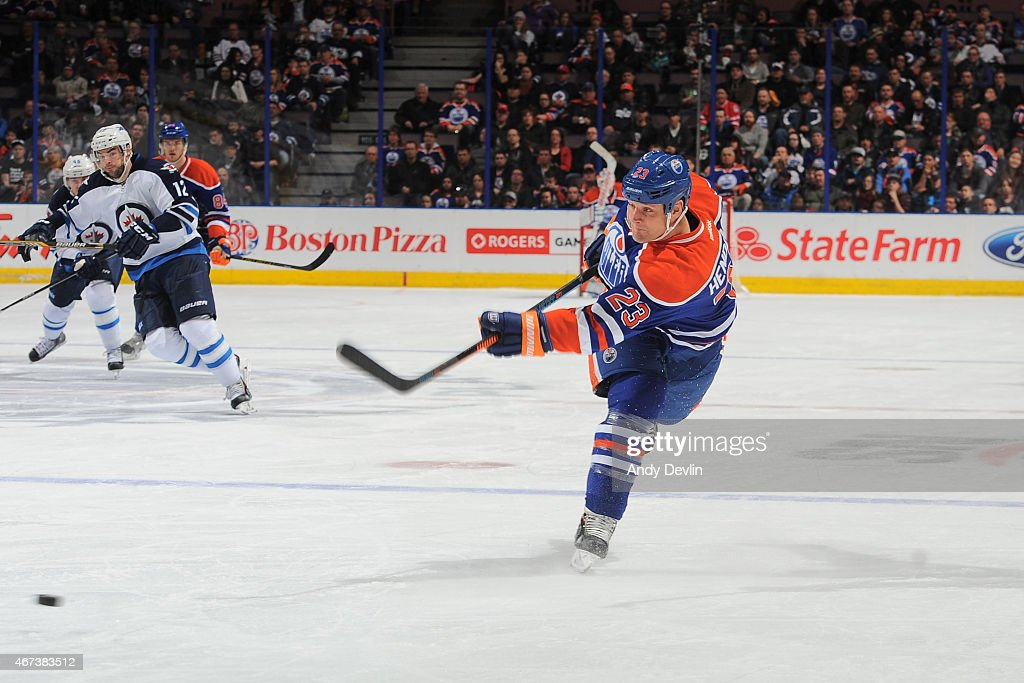 Matt Hendricks of the Edmonton Oilers takes a shot during the game against the Winnipeg Jets on March 23 2015 at Rexall Place in Edmonton Alberta...