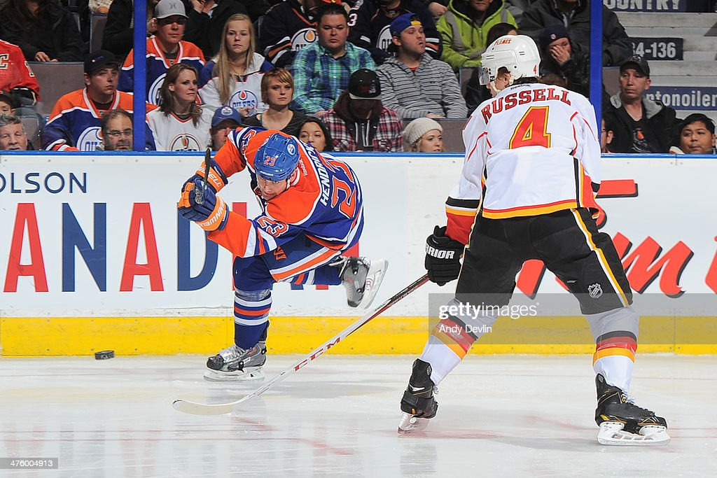 <a gi-track='captionPersonalityLinkClicked' href=/galleries/search?phrase=Matt+Hendricks&family=editorial&specificpeople=4537275 ng-click='$event.stopPropagation()'>Matt Hendricks</a> #23 of the Edmonton Oilers takes a shot past <a gi-track='captionPersonalityLinkClicked' href=/galleries/search?phrase=Kris+Russell&family=editorial&specificpeople=879805 ng-click='$event.stopPropagation()'>Kris Russell</a> #4 of the Calgary Flames on March 1, 2014 at Rexall Place in Edmonton, Alberta, Canada.