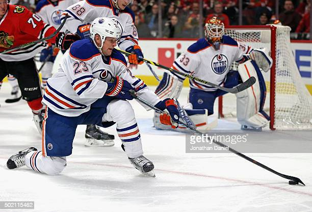 Matt Hendricks of the Edmonton Oilers tries to control the puck from one knee against the Chicago Blackhawks at the United Center on December 17 2015...