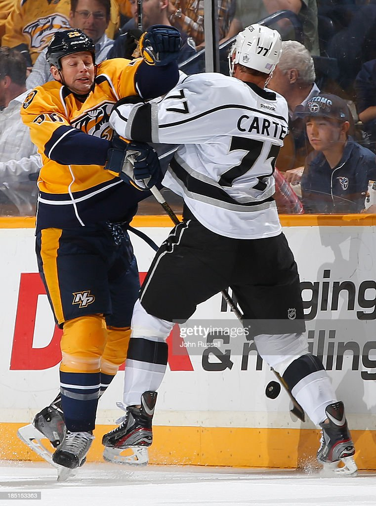 Matt Hendricks #26 of the Nashville Predators battles along the boards against Jeff Carter #77 of the Los Angeles Kings at Bridgestone Arena on October 17, 2013 in Nashville, Tennessee.