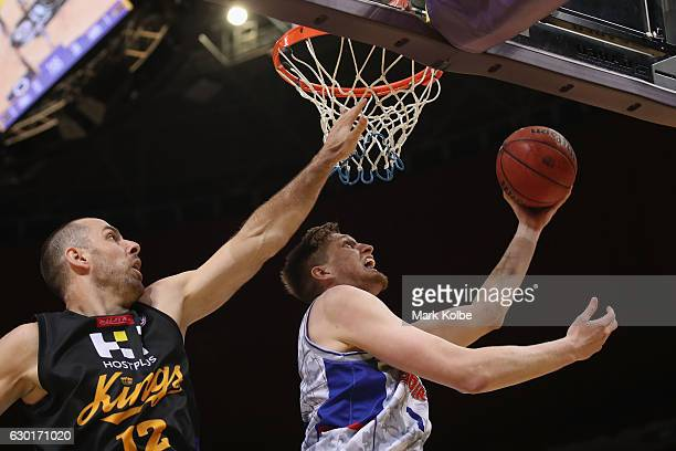 Matt Hodgson of the Adelaide 36ers lays up a shot under pressure from Aleks Maric of the Kings during the round 11 NBL match between Sydney and...
