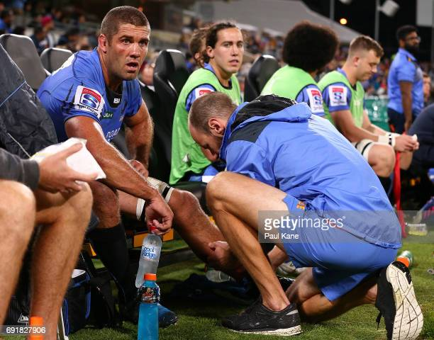 Matt Hodgson of the Force receives treatment to his lower leg after being substituted out of the game during the round 15 Super Rugby match between...