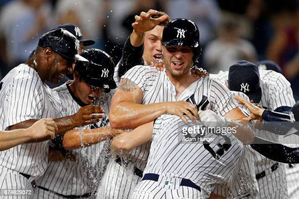 Matt Holliday of the New York Yankees is congratulated by teammates after hitting the game winning 3run home run against the Baltimore Orioles during...