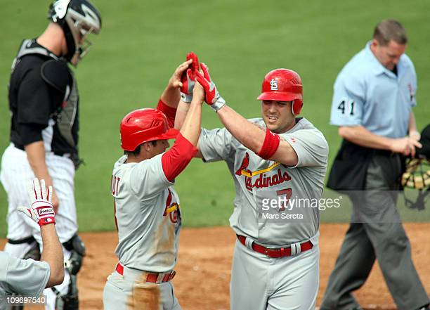 Matt Holliday of the St Louis Cardinals celebrates his two run home run against the Florida Marlins with teammate Ryan Theriot at Roger Dean Stadium...