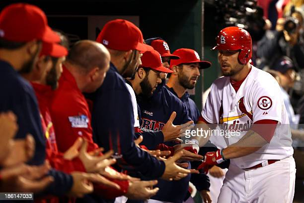 Matt Holliday of the St Louis Cardinals celebrates with teammates in the dugout after hitting a solo home run in the fourth inning against the Boston...