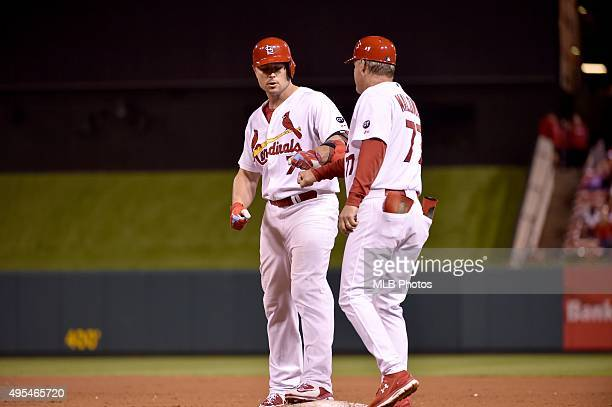 Matt Holliday of the St Louis Cardinals gives a fist bump to first base coach Chris Maloney after getting a base hit for his 45th consecutive game...
