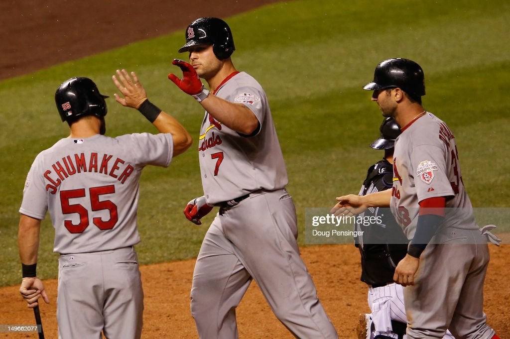 Matt Holliday of the St Louis Cardinals is welcomed home by Skip Schumaker and Daniel Descalso of the Cardinals after his three run home run off of...