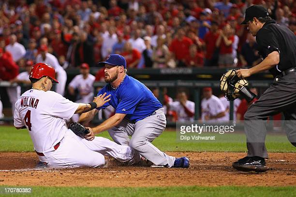 Matt Holliday of the St Louis Cardinals scores a run against starting pitcher Travis Wood of the Chicago Cubs on a wild throw to home in the seventh...