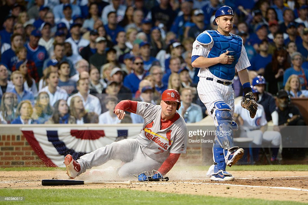 Matt Holliday of the St Louis Cardinals scores a run in the fourth inning as Miguel Montero of the Chicago Cubs looks on during game three of the...