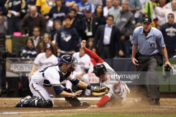 Matt Holliday of the St Louis Cardinals scores on a sacrifice fly by Nick Punto in the top of the third inning against catcher Jonathan Lucroy of the...