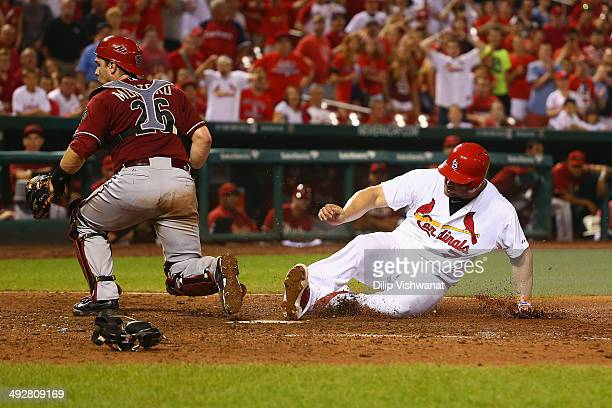 Matt Holliday of the St Louis Cardinals scores the gamewinning run on an errant throw to Miguel Montero of the Arizona Diamondbacks in the twelfth...