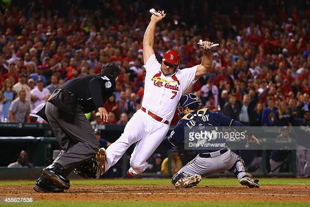 Matt Holliday of the St Louis Cardinals scores the gamewinning run against Jonathan Lucroy of the Milwaukee Brewers in the seventh inning at Busch...