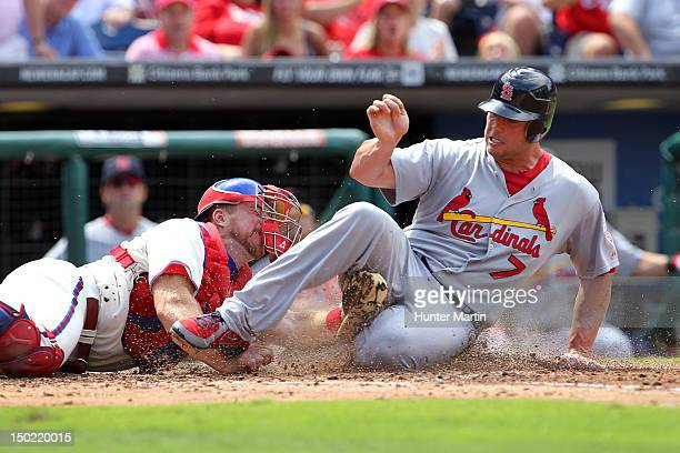 Matt Holliday of the St Louis Cardinals slides under the tag of Erik Kratz of the Philadelphia Phillies during a game at Citizens Bank Park on August...